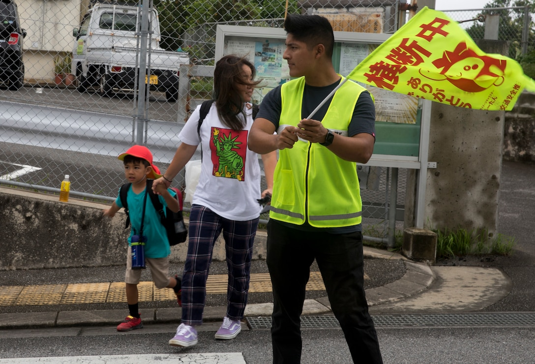 U.S. Marine Corps Pfc. Alfonso Padilla, guides a local elementary school child and his mother at a crosswalk July 18, 2019. Crossing guard duty is one of the multiple tasks conducted by Marine volunteers on Okinawa.