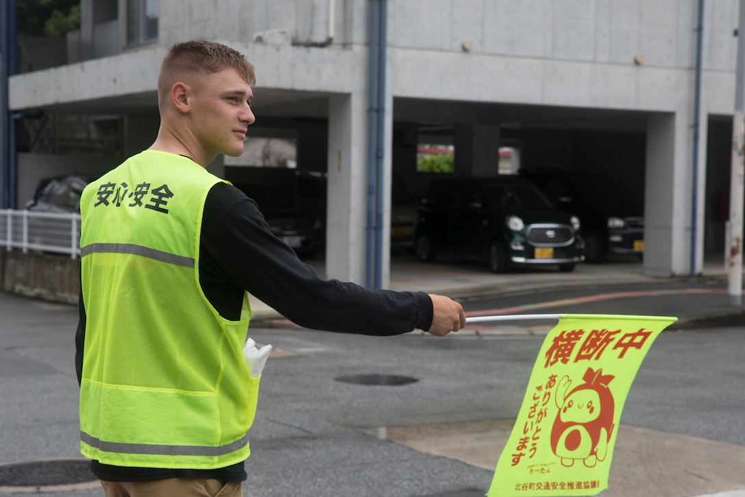 U.S. Marine Corps Lance Cpl. Timothy, observes traffic while conducting crossing guard duty July 18, 2019. Cross guard volunteer opportunities are one of the multiple tasks   Marines on camp guard duty partake in.