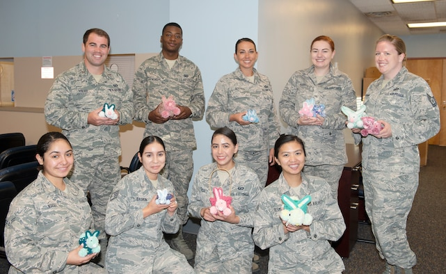 "Members of 55th Comptroller Squadron Financial Management flight pose with crocheted rabbits made by Sally Harder July 1, 2019, at Offutt Air Force Base, Nebraska. Harder, a retired military spouse and grandmother to Airman 1st Class Julie Hubble, financial services technician enjoys crafting for others.  ""I've been making things for people all of my life it's just little things to brighten up their desk,"" said Harder."