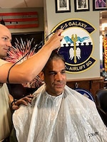 Without hesitation, 312th Airlift Squadron teammates transformed their heritage room into a makeshift barbershop and administered basic training style shearing in support of Master Sgt. Steve Hatfield.
