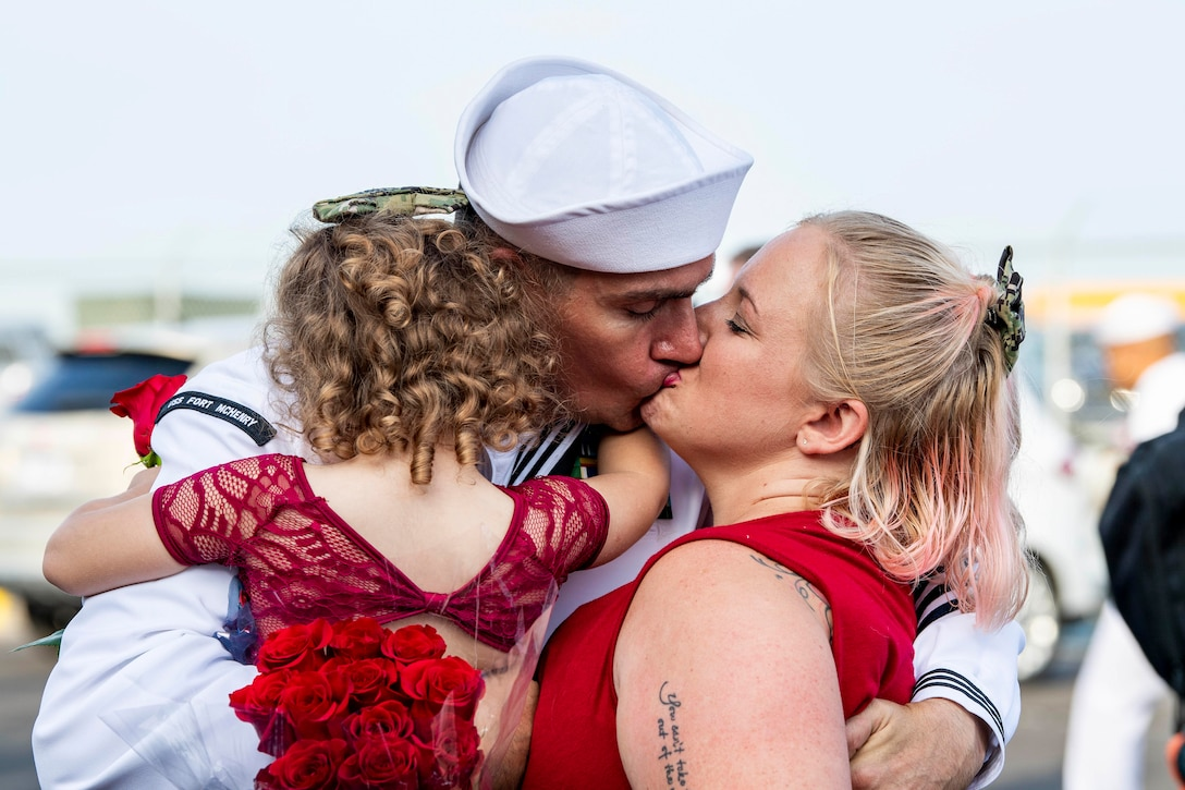 A sailor kisses a woman while holding a child.
