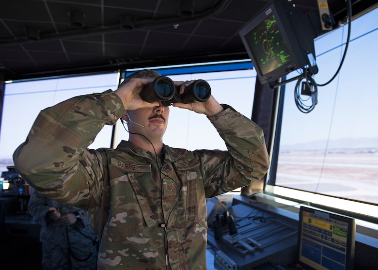 Staff Sgt. George Garrett, 56th Operation Support Squadron air traffic controller, scans the horizon for a pair of F-35 Lightning II aircraft returning from a mission from the Air Traffic Control Tower July 15, 2019, at Luke Air Force Base, Ariz.