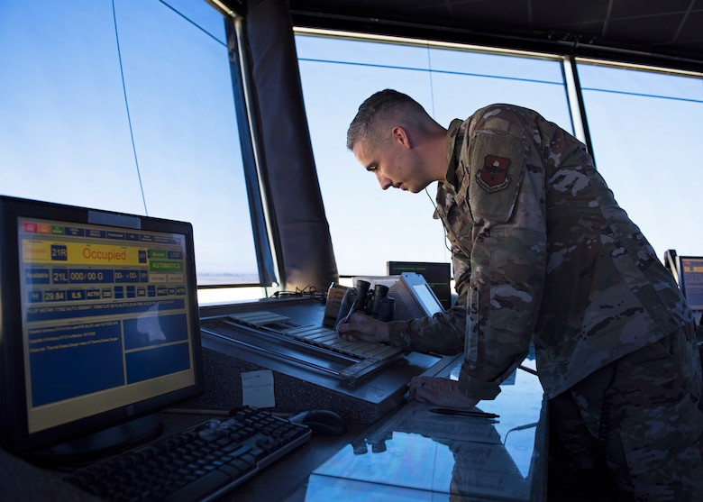 Staff Sgt. George Garrett, 56th Operation Support Squadron air traffic controller, writes down information on a flight progress strip in the Air Traffic Control Tower July 15, 2019, at Luke Air Force Base, Ariz.