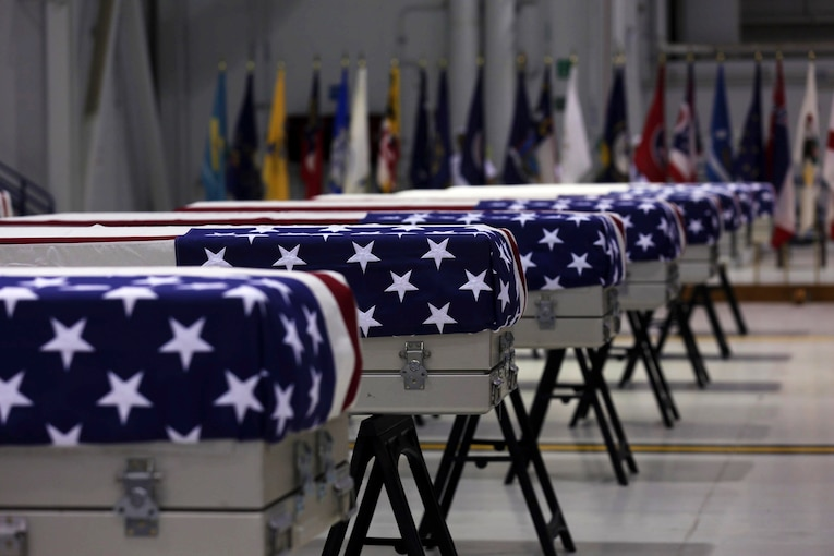 A group of flag-draped caskets sit in a building.