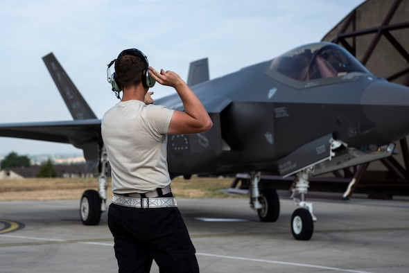 U.S. Air Force Airman 1st Class Cody Albert, 421st Fighter Squadron crew chief, marshals an F-35A Lightning II during Operation Rapid Forge at Spangdahlem Air Base, Germany, July 18, 2019. Rapid Forge aircraft are forward deploying to the territory of NATO allies to improve interoperability. The goal of the operation is to increase the readiness and responsiveness of U.S. forces in Europe and assist allies to increase regional security. (U.S. Air Force photo by Airman 1st Class Valerie Seelye)
