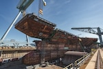 NEWPORT NEWS, Va. (July 10, 2019) The final piece of the flight deck of the future USS John F. Kennedy (CVN 79) is lifted into place at Huntington Ingalls Industries' Newport News Shipbuilding Division in Newport News, Va., July 10. The addition of the 780-ton upper bow section is one of the last steel structural units, known as superlifts, to be placed on Kennedy, which is on schedule to be launched in late 2019.
