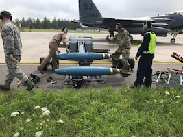 Airmen from the 435th Contingency Response Group and an F-15E Strike Eagle from the 4th Fighter Wing, Seymour Johnson Air Force Base, North Carolina, perform a forward rearming mission with inert munitions during Operation Rapid Forge at Siauilai Air Base, Lithuania, July 18, 2019. (Courtesy photo)