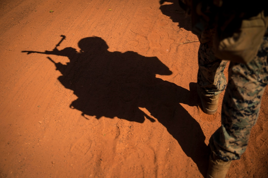 The leg and shadow of a Marine is shown against dry clay ground.