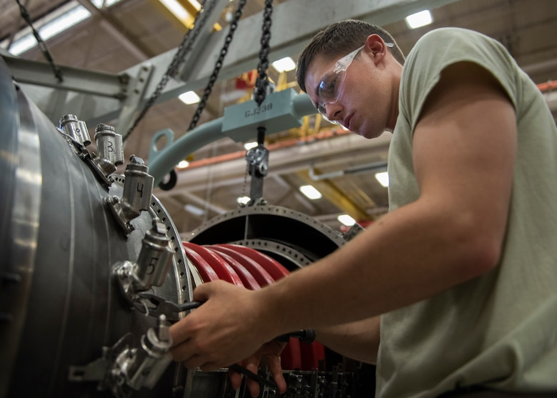 Airman Alex Volpe, 361st Training Squadron aerospace propulsion apprentice course student, removes safety wires from a F110 turbine engine at Sheppard Air Force Base, Texas, July 18, 2019. Volpe is a native to Canton, Ohio, and is attending technical training at Sheppard AFB. In this block of training he is learning how to remove and re-install the fuel nozzle section of the engine. The first step to removing it, is removing the safety wires which is used to secure most parts on the engine. (U.S. Air Force photo by Airman 1st Class Pedro Tenorio)