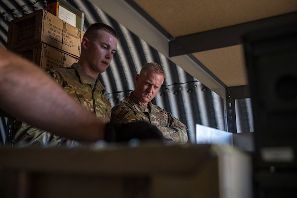 U.S. Air Force Airman 1st Class Thomas Knight, 325th Maintenance Squadron stockpile surveillance crew chief, shows Col. Brian Laidlaw, 325th Fighter Wing commander, how munitions are organized at Tyndall Air Force Base, Florida, July 17, 2019.