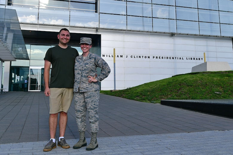 An Airman stands next to her husband in front of the library she will be interning at.