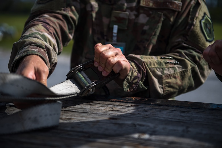 U.S. Air Force Col. Brian Laidlaw, 325th Fighter Wing commander, straps a box of munitions to a flatbed at Tyndall Air Force Base, Florida, July 17, 2019.