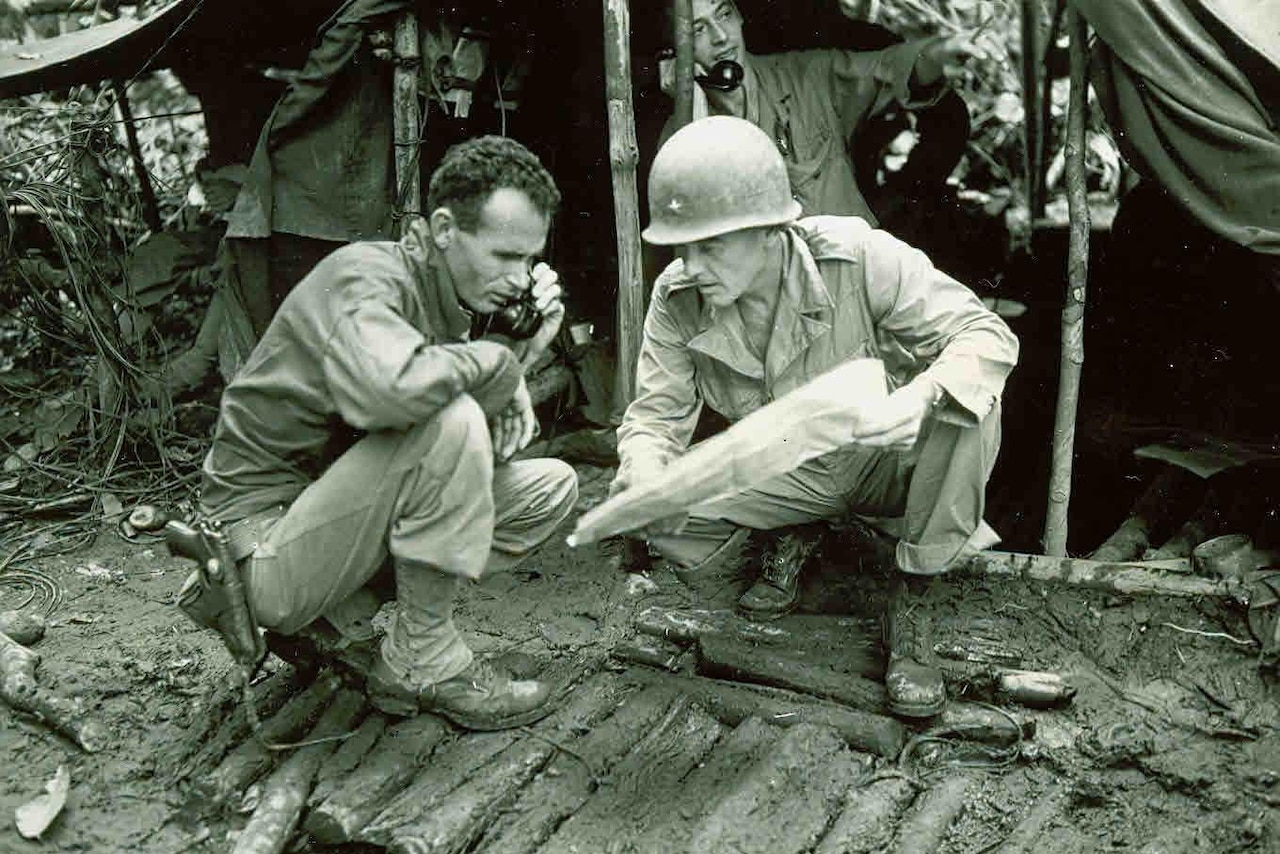 Two soldiers huddle together beside a mud hut, both looking at a map. One is pointing at the map while the other has a phone to his ear.