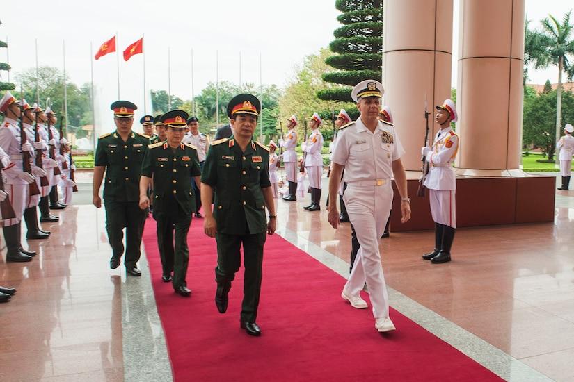 Men walk down red carpet.