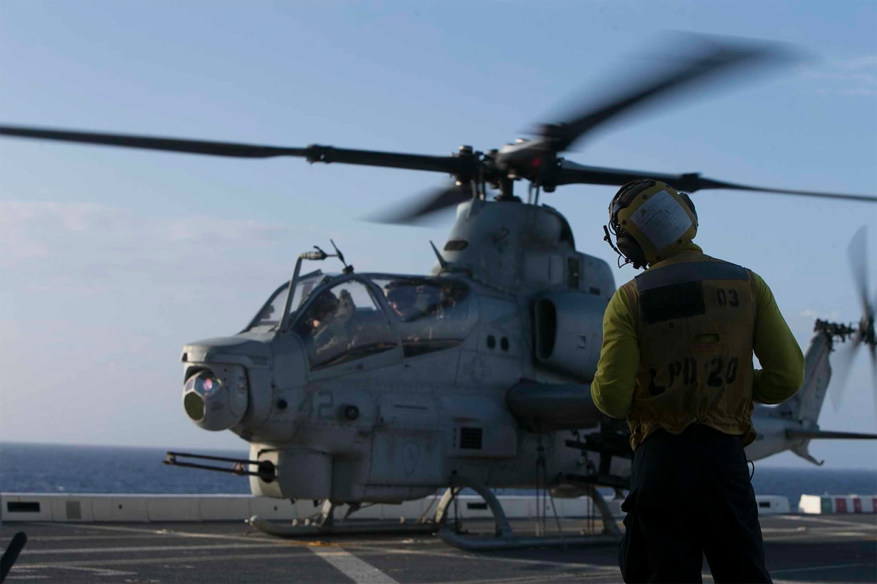 Helicopter whirls on ship at sea.