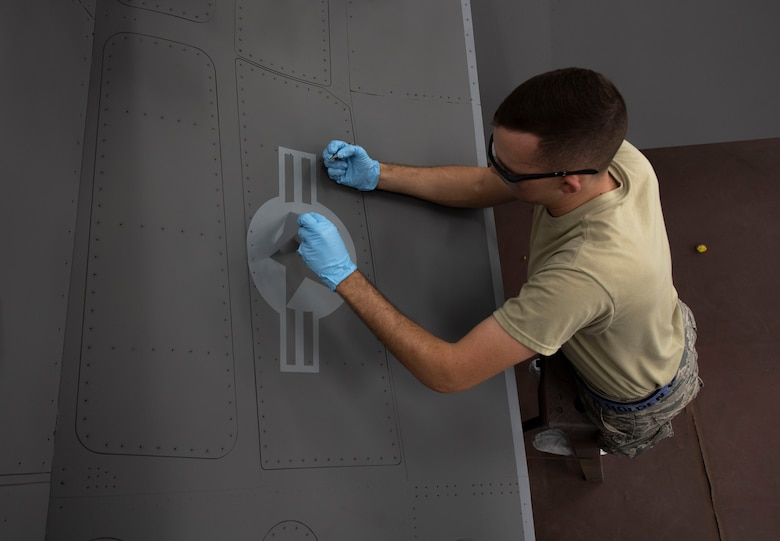 U.S. Air Force Airman 1st Class Holden Nieman, 20th Equipment Maintenance Squadron aircraft structural maintainer, peels a stencil off the side of an F-16CM Viper at Shaw Air Force Base, South Carolina, June 20, 2019.