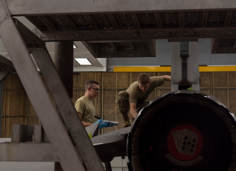 U.S. Air Force Airman 1st Class Holden Nieman and Senior Airman Daniel Meadows, 20th Equipment Maintenance Squadron aircraft structural maintainers, work together to paint a decal on the side of an F-16CM Viper at Shaw Air Force Base, South Carolina, June 20, 2019.