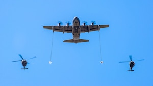 Two HH-60 Pave Hawk helicopters fly in formation with a C-130 Hercules