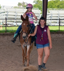 Olivia Byers rides a horse led by Sofia Perez-Gomez during the Joint Base San Antonio Exceptional Family Member Program Equestrian Camp, held at the JBSA-Fort Sam Houston Equestrian Center June 25-27. Byers was one of 12 children who participated in the camp, which allowed special needs children from military families and their siblings to learn about horsemanship and to ride horses. Perez-Gomez served as a camp volunteer.