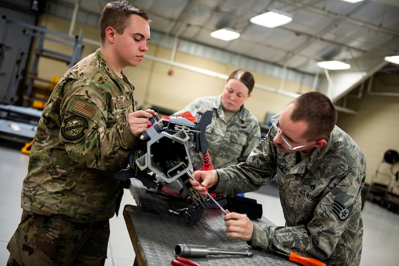 Senior Airman Sydney Starkey, left, 23d Maintenance Squadron (MXS) armament (ARMs) flight alternate mission equipment (AME) element member, Airman 1st Class Hadleigh Brabbin, center, 23d MXS ARM AME element member, and Staff Sgt. Arthur Vigil, 23d MXS ARM AME floor supervisor, remove a bracket from a triple ejector rack for maintenance, July 17, 2019, at Moody Air Force Base, Ga. The ARMs shop primarily performs quality armament systems maintenance and inspections to provide aircrews with safe and reliable weapon systems for lethal airpower employment. (U.S. Air Force photo by Senior Airman Erick Requadt)