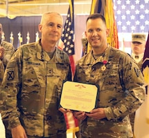 Maj. Gen. John P. Sullivan, commanding general of 1st Theater Sustainment Command, presents Col. Jeffrey McCarter, 8th Medical Brigade commander, with the Legion of Merit award before a transfer of authority ceremony between 8th Medical Brigade and 3d Medical Command Deployment Support - Forward at Camp As Sayliyah, Qatar, July 18, 2019.