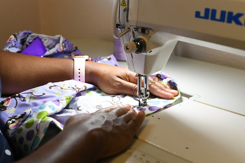 Master Sgt. (Ret.) Keena Alston, 916th Air Refueling Wing commander's secretary, works fabric through a sewing machine on July 12, 2019. Alston makes dresses that are delivered to vulnerable children all around the world by missionary volunteers. (US Air Force Photo by Jeramy Moore)