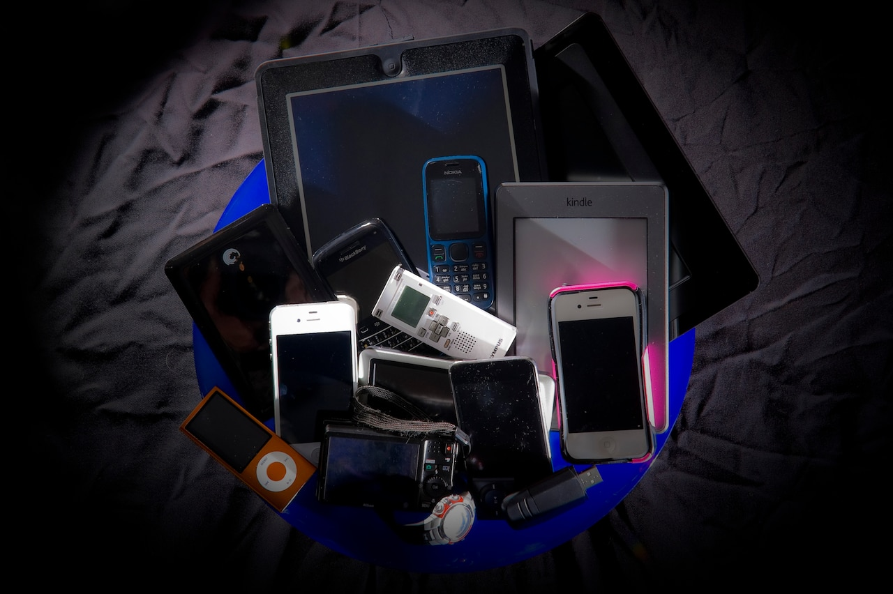 A pile of electronic devices including cell phones, tablets, recorders.
