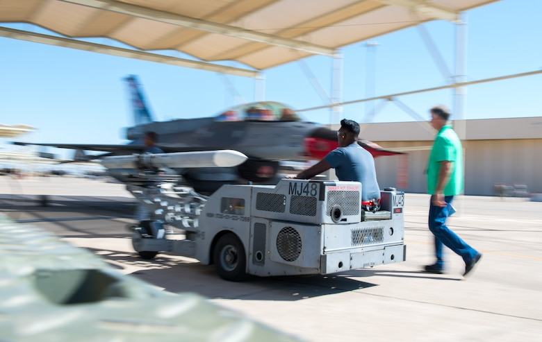 ME-2 Eswaran Thiagarajah, 425th Aircraft Maintenance Unit load crew member, drives an inert bomb into position to be loaded onto an F-16 Fighting Falcon during the 2nd Quarter Load Crew Competition at July 18, 2019, at Luke Air Force Base, Ariz.