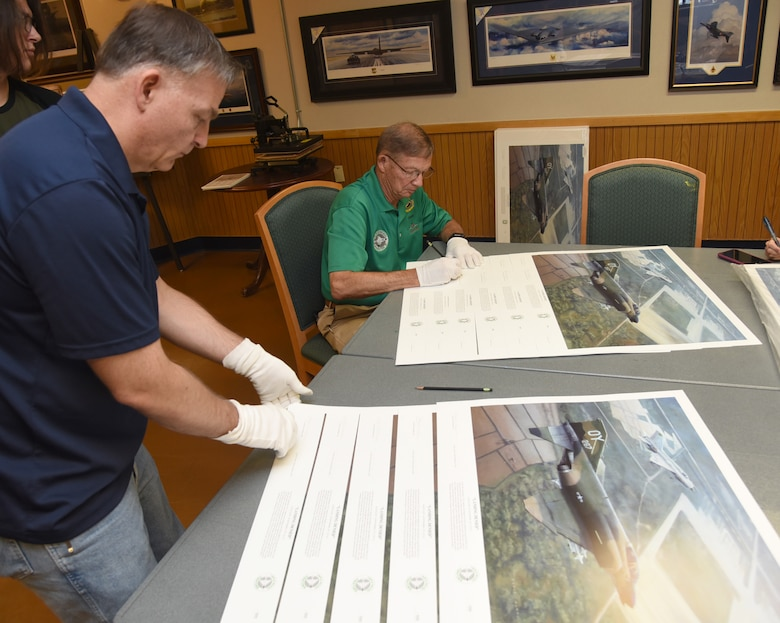 "United States Air Force Aviation Artist Darby Perrin and Vietnam War Ace Col. Chuck DeBellevue carefully arrange and sign 555 copies of the piece Perrin painted for DeBellevue, entitled ""Landing Denied."" The piece is of a scene on Sept. 9, 1972,  when then Capt. DeBellevue and Capt. John Madden were in close proximity of a MiG 21J over Phuc Yen Airbase. (U.S. Air Force photo/Kelly White)"