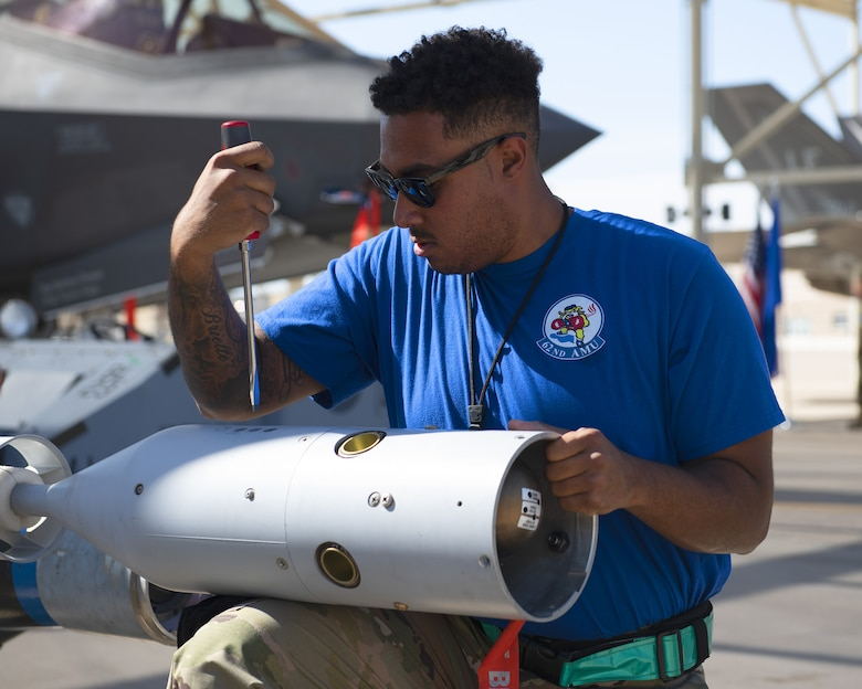 Staff Sgt. Jeromie Gathers, 62nd Aircraft Maintenance Unit load crew member, makes adjustments to an inert bomb July 18, 2019, at Luke Air Force Base, Ariz.