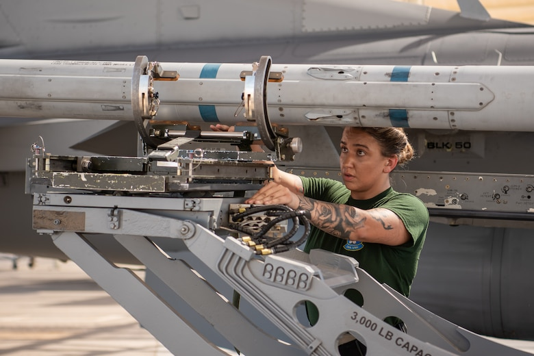 Staff Sgt. Katrina Stuhl, 310th Aircraft Maintenance Unit load crew member, loads a bomb onto an F-16 Fighting Falcon, July 18, 2019, at Luke Air Force Base, Ariz.