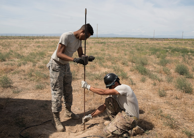U.S Air Force Airman 1st Class Miles Swammi, 726th Air Control Squadron radar systems technician, and U.S. Air Force Airman Tech. Sgt. Jacob Jacques, 726th ACS radar systems technician, install a grounding rod during the 726th ACS Hardrock Exercise 19-2, July 16, 2019, at Mountain Home Air Force Base, Idaho. The 726th ACS plays a vital role in the communication capabilities between personnel. (U.S. Air Force photo by Senior Airman Tyrell