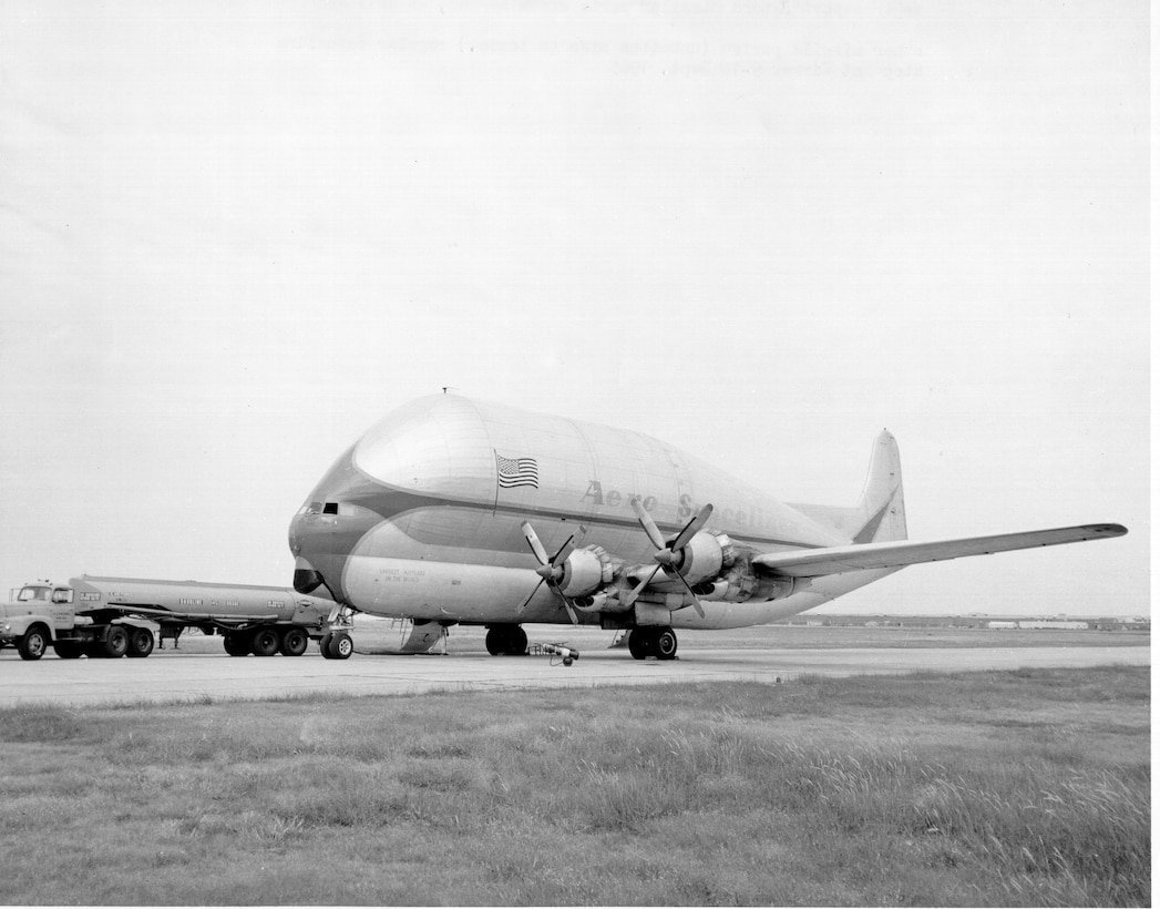 """The Aero Spacelines Inc.'s B-377PG """"Pregnant Guppy"""" shown at Tinker Air Force Base in the mid-1960s with well-worn markings as the aircraft provided outsized cargo transport in support of the Apollo program. Barely visible on the nose is the wording, """"Largest Airplane In The World."""" The C-97 variant was flown to NASA's Dryden facility at Edwards Air Force Base for tests and evaluation by pilots Joe Vensel and Stan Butchart in October 1962. The outsized cargo aircraft incorporated the wings, engines, lower fuselage and tail from a Boeing 377 Stratocruiser with a huge upper fuselage more than 20 feet in diameter. The modified aircraft was built primarily to carry portions of the Saturn 5 rockets from the manufacturer to Cape Canaveral."""