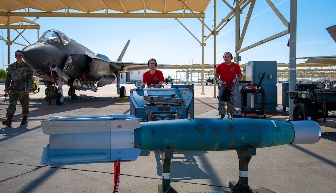 Airman 1st Class Michael Zambrano, 63rd Aircraft Maintenance Unit weapons load crew member (center), loads an inert bomb onto a jammer with his team member, Staff Sgt. Kevin McCain, 63rd AMU load crew team chief July 18, 2019, at Luke Air Force Base, Ariz.