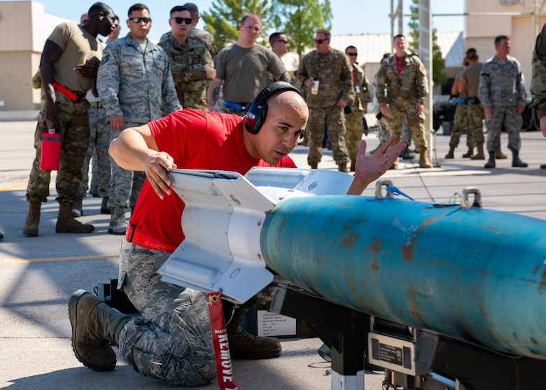 Staff Sgt. Kevin McCain, 63rd Aircraft Maintenance Unit load crew team chief, handles an inert bomb July 18, 2019, at Luke Air Force Base, Ariz.