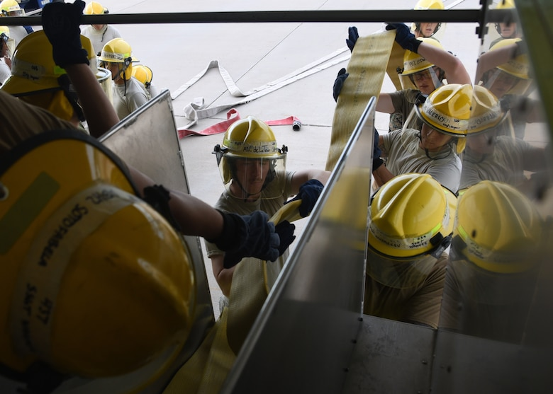 U.S. Military students from 312th Training Squadron practice unraveling fire hoses efficiently from the back of a fire truck outside the Louis F. Garland Department of Defense Fire Academy on Goodfellow Air Force Base, Texas, July 11, 2019. Students were trained in a stress-induced environment to practice valuable skills such as remaining calm, working in teams and effective communication, all of which are needed in real-life firefighting scenarios.  (U.S. Air Force Photo by Airman 1st Class Abbey Rieves/Released)