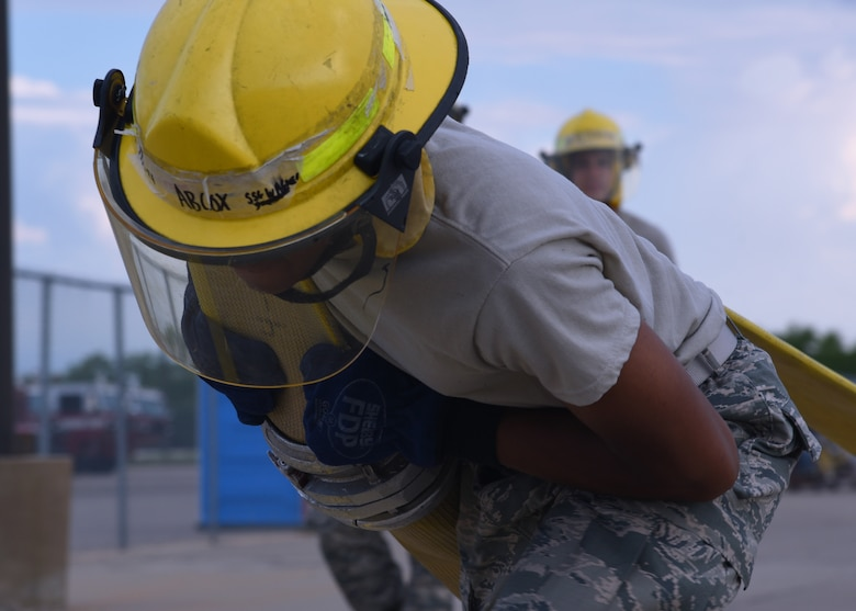 U.S. Air Force Airman Keundra Cox, 312th Training Squadron student, heaves a fire hose out of a fire truck and sprints it to a marked location outside the Louis F. Garland Department of Defense Fire Academy on Goodfellow Air Force Base, Texas, July 11, 2019. Cox and his classmates took turns running the fire hose, learning the strength, endurance and momentum needed to get the hose 100 yards, much like they will outside of the technical training environment. (U.S. Air Force Photo by Airman 1st Class Abbey Rieves/Released)