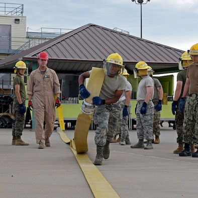 U.S. Military students from the 312th Training Squadron, in the firefighter training course, complete a drill in which they must run a fire hose out 100 meters at the Louis F. Garland Department of Defense Fire Academy on Goodfellow Air Force Base, Texas, July 11, 2019. The students complete drills such as this to build strength and endurance to complete their duties. (U.S. Air Force photo by Airman 1st Class Robyn Hunsinger/Released)