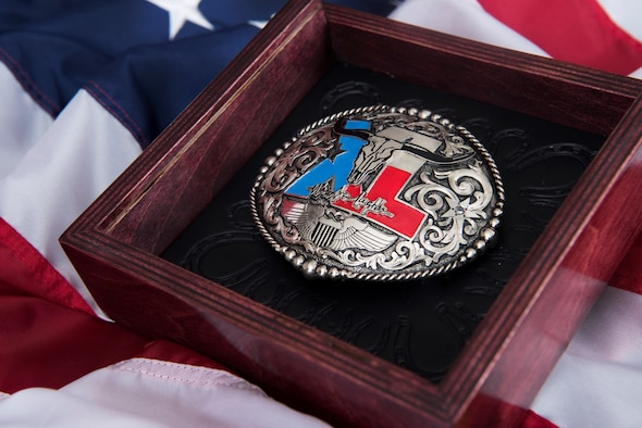 A custom belt buckle, designed for the wing's newly inducted lifetime Honorary Commander lays in its shadow box at Laughlin Air Force Base, Texas, July 17, 2019. Nominations for this elite lifetime program, formally known as Laughlin's Wings of Amistad, are not guaranteed during each commander's tenure; however, each nominee exhibits a lifetime impact on this base community. (U.S. Air Force photo by Airman 1st Class Marco A. Gomez)
