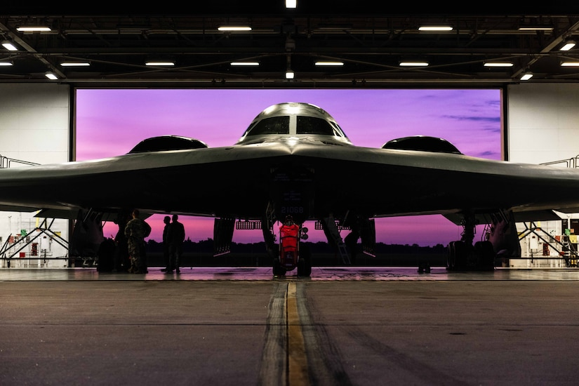 A B-2 Spirit aircraft sits in front of a purple screen a hangar .