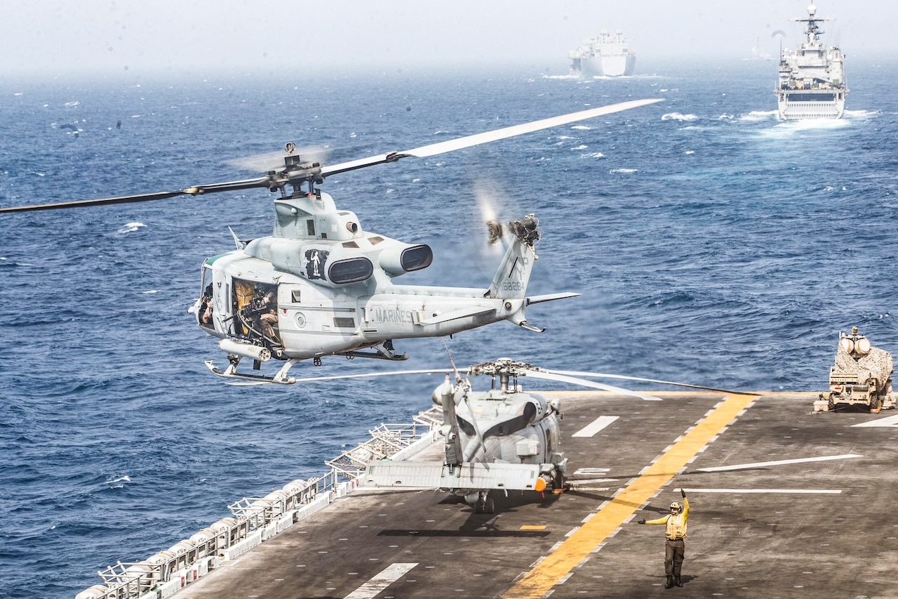 A helicopter takes off as ships sail the sea.