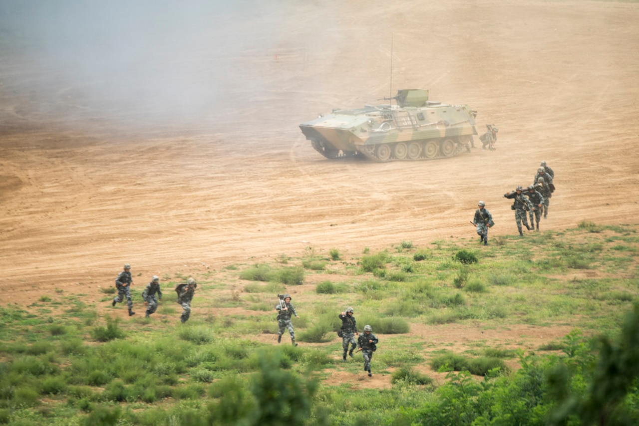 Troops and tracked vehicle move across terrain.