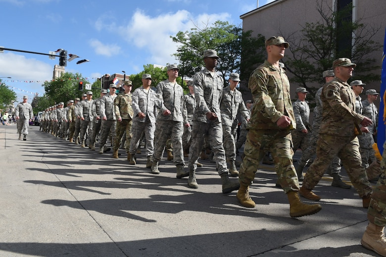 Airmen from F.E. Warren Air Force Base, Wyo., march in formation during the 123rd Cheyenne Frontier Days opening Grand Parade in Cheyenne, Wyo., July 21, 2018. Service members from multiple branches took part in the parade, as well as a number of civic and veteran service organizations. This year marks the 152nd anniversary of F.E. Warren Air Force Base and the city of Cheyenne. The F.E. Warren Air Force Base and Cheyenne communities came together to celebrate the CFD rodeo and festival, which runs from July 20-29. (U.S. Air Force photo illustration by Senior Airman Breanna Carter)