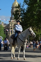 Chief MSgt. Jennifer Lovering, 153rd Communications Flight operations superintendent, rides her horse at the capitol building during the Grand Parade, July 20, 2019. This year marks the 152nd anniversary of F.E. Warren Air Force Base and the city of Cheyenne. The F.E. Warren Air Force Base and Cheyenne communities came together to celebrate the CFD rodeo and festival, which runs from July 19-28. (U.S. Air Force photo by Staff Sgt. Ashley N. Sokolov)