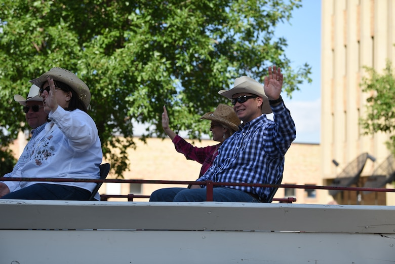 Major General Fred Stoss, 20th Air Force commander, and Col. Peter Bonetti, 90th Missile Wing commander, along with their famillies, wave at the crowd during the 123rd Cheyenne Frontier Days opening Grand Parade in Cheyenne, Wyo., July 20, 2019. The Cheyenne community and F.E. Warren Air Force Base have been working together for 123 years to keep the Daddy of 'em All, running smoothly. (U.S. Air Force photo by Staff Sgt. Ashley N. Sokolov)