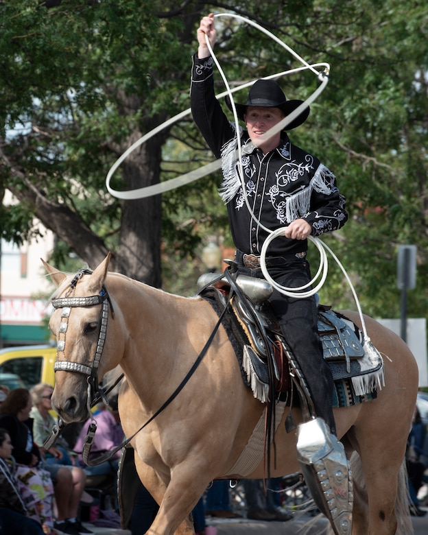 A cowboy roper performs lasso tricks during the Grand Parade in Cheyenne, Wyo., July 20, 2019. The F.E. Warren Air Force Base and Cheyenne communities came together to celebrate the CFD rodeo and festival, which runs from July 19-28. (U.S. Air Force photo by Senior Airman Abbigayle Willams )