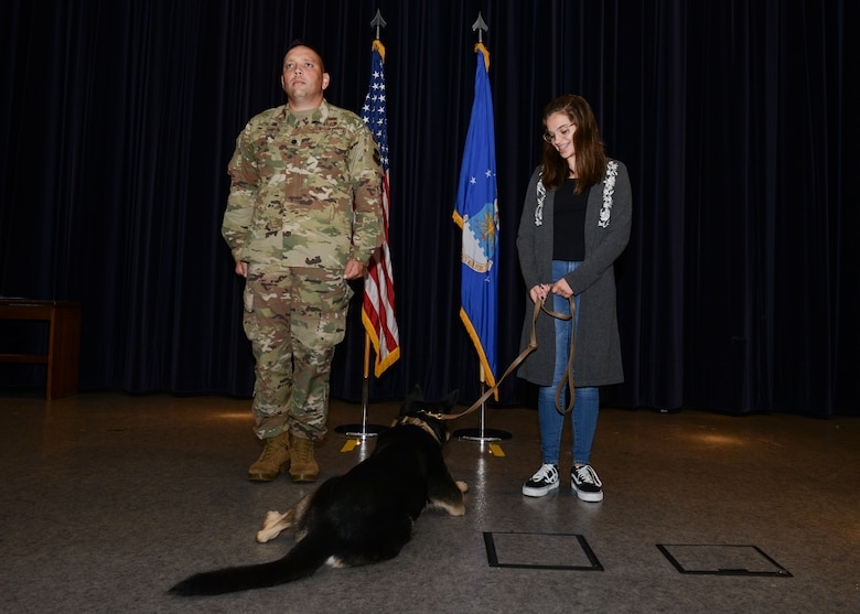 U.S. Air Force Lt. Col. Jesse Goens, 31st Security Forces Squadron commander, and Megan Lasica stand with Military Working Dog Cigan during a retirement ceremony at Aviano Air Base, Italy, July 19, 2019. MWD Cigan received an Air Force Achievement Medal for his work since 2015 at Aviano AB. (U.S. Air Force photo by Staff Sgt. Rebeccah Woodrow)
