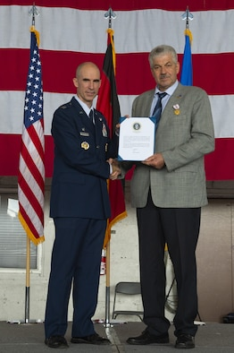U.S. Air Force Col. Jason Bailey, 52nd Fighter Wing commander, presents a presidential congratulatory retirement letter to Mr. Klaus Rodens, 52nd Mission Support Group works council chairman, at Spangdahlem Air Base, Germany, July 19, 2019. Rodens contributed to the establishment of mutual trust and cooperation between the German communities in the vicinity of Spangdahlem AB and 52nd FW Airmen. (U.S. Air Force photo by Airman 1st Class Branden Rae)