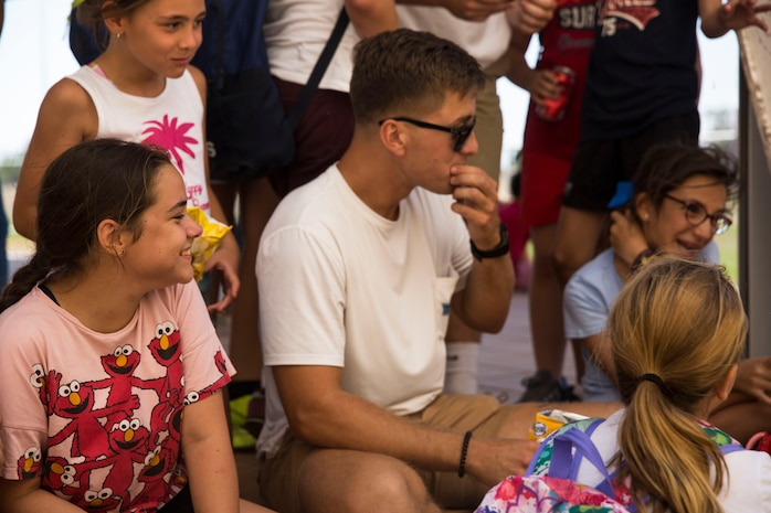 A U.S. Marine with Special Purpose Marine Air-Ground Task Force Crisis Response-Africa 19.2, Marine Forces Europe and Africa, eats lunch with students from La Inmaculada charter school during a community relations event on Moron Air Base, Spain, July 2, 2019. Marines and Sailors of SPMAGTF-CR-AF played various American games with the students such as cornhole, football, and baseball while speaking English to help increase the students' fluency in the language. Community relations events like this help strengthen relationships between the local communities and the deployed Marines. SPMAGTF-CR-AF is deployed to conduct crisis-response and theater-security cooperation operations in Africa and promote regional stability by conducting military-to-military training exercises throughout Europe and Africa. (U.S. Marine Corps photo by Cpl. Margaret Gale)