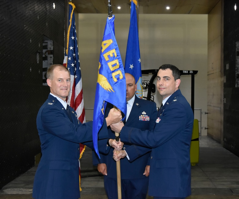Incoming AEDC Flight Systems Combined Test Force Director Lt. Col. John McShane, right, accepts the Flight Systems CTF guidon from AEDC Test Operations Division Chief Col. Keith Roessig during a June 28 Change of Leadership ceremony in the Propulsion Wind Tunnel Model Installation Building at Arnold Air Force Base. McShane comes to Arnold from Washington, D.C., where he most recently served as a Program Element Monitor for Advanced Aircraft Technology at the Directorate of Special Programs, Assistant Secretary of the Air Force (Acquisition, Technology & Logistics), at the Pentagon. (U.S. Air Force photo by Bradley Hicks)